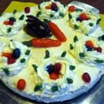Saftiger Karottenkuchen österlich dekoriert mit Marzipankarotten und bunten Ostereiern.